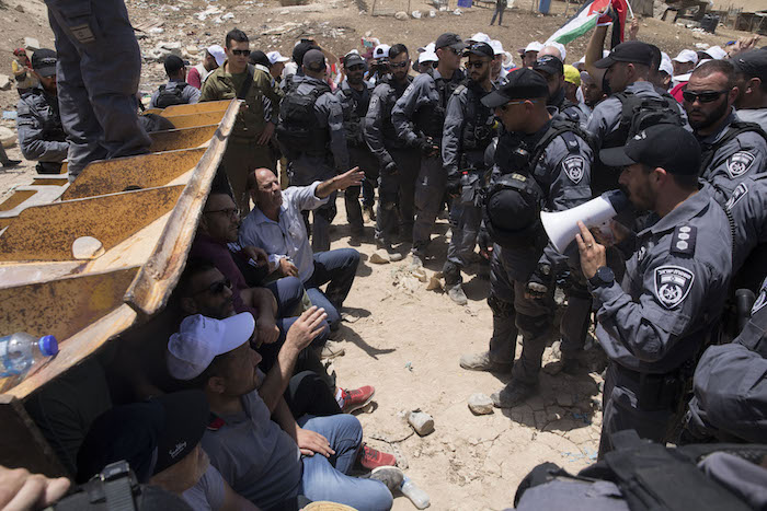 Palestinian activists and residents of Khan al-Ahmar block the path of Israeli security forces and bulldozers, as the latter tried to pave an access road to allow for the village's imminent demolition, July 4, 2018. (Oren Ziv)