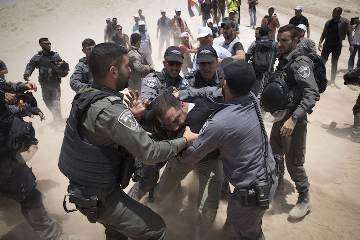 Israeli security forces arrest a protester in the Bedouin village of Khan al-Ahmar in the West Bank, July 4, 2018. (Oren Ziv)