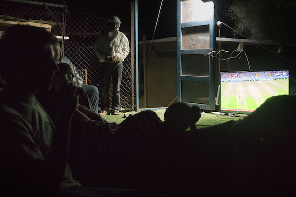 Villagers and activists watch a World Cup match together in Khan al-Ahmar's schoolyard, July 2, 2018. (Oren Ziv)