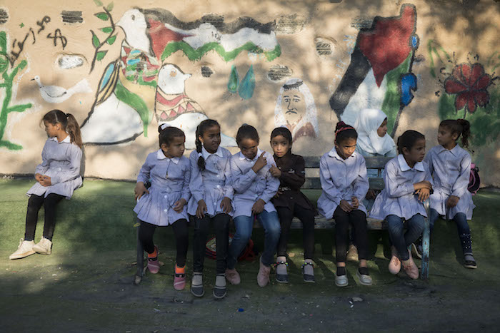 Palestinian schoolgirls sit outside the school in Khan al-Ahmar, which held its first day of school a month and a half early in order to prevent its planned demolition, July 16, 2018. (Oren Ziv)