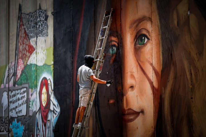 A man paints a mural of Palestinian Ahed Tamimi on a part of the West Bank separation wall in the West Bank city of Bethlehem, July 25, 2018. (Wisam Hashlamoun/Flash90)