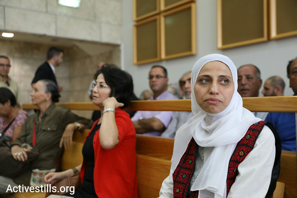 Palestinian poet Dareen Tatour (right) seen with MK Haneen Zoabi in Nazareth Magistrate's Court after the former is sentenced to five months, including time served, for a poem she wrote on Facebook. (Oren Ziv/Activestills.org)