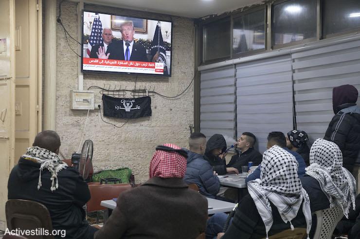 Palestinian men watch Donald Trump give a foreign policy speech in a cafe in East Jerusalem, December 6, 2017. (Oren Ziv/Activestills.org)