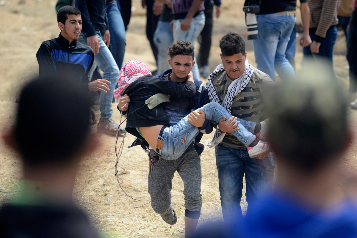 Palestinian youth carry a wounded boy to receive medical care during the Great Return March along the Gaza-Israel border, April 27, 2018. (Mohammed Zaanoun/Activestills.org)