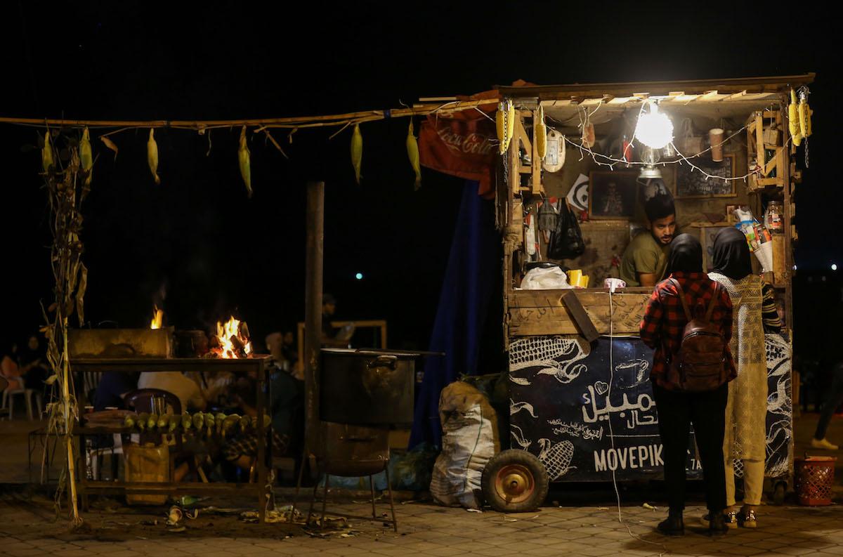 Palestinian women speak with a street vendor on Gaza City's beachside promenade. (Mohamed Al Hajjar)