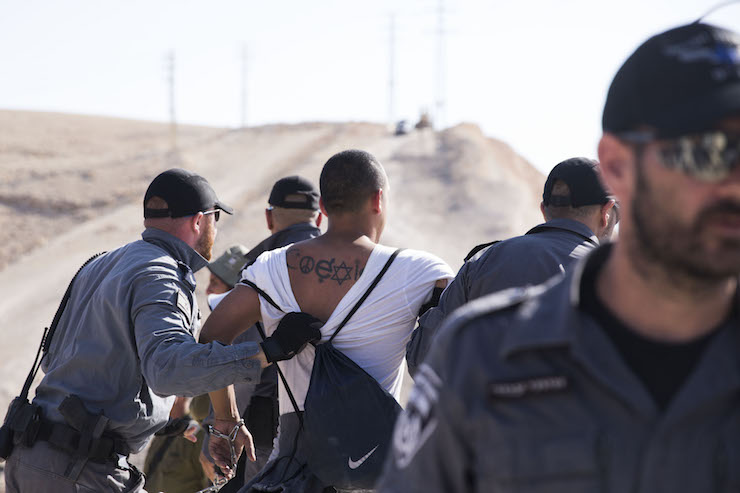 Israeli police arrest an international solidarity activist who had attempted to block a bulldozer brought to prepare for the demolition of Khan al-Ahmar, July 5, 2018. (Oren Ziv/Activestills.org)