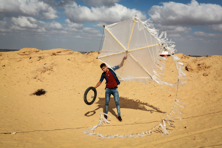 A Palestinian youth in southern Gaza is seen preparing to send an incindiary kite toward the border with Israel, June 29, 2018. (Abed Rahim Khatib/Flash90)