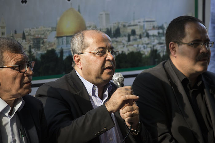 MK Ahmad Tibi (Joint List) speaks during a press conference outside Khan al-Ahmar's school on the first day of the school year, July 16, 2018. (Oren Ziv)