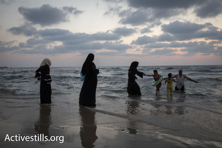 Palestinians from the West Bank swim in the Mediterranean Sea during Eid al-Adha, Tel Aviv, August 22, 2018. (Oren Ziv)