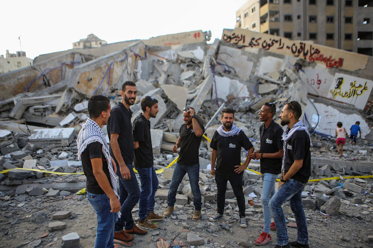 Members of Al-Anqaa, a Palestinian folklore troupe, perform on the rubble of Al-Meshal Cultural Center. (Mohamed Al Hajjar)