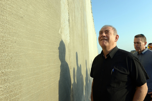 Prime Minister Benjamin Netanyahu visits the separation wall near Tarqumiya in the West Bank, July 20, 2016. (Haim Zach/GPO)