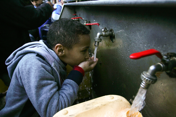 Palestinians fill water from pipes provided by the United Nations Relief and Works Agency (UNRWA) headquarters in the Rafah refugee camp in the Southern Gaza Strip on January 6, 2018. (Abed Rahim Khatib/Flash90)