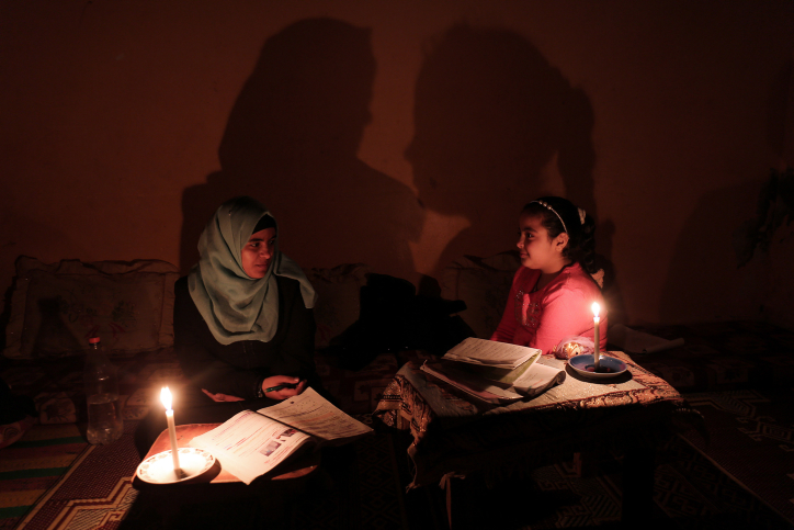 Palestinian schoolgirls do their homework by candlelight at their home in Rafah refugee camp, in the southern Gaza Strip, on February 15, 2018. The Gaza power plant stopped working due to lack of fuel. (Abed Rahim Khatib/Flash90)