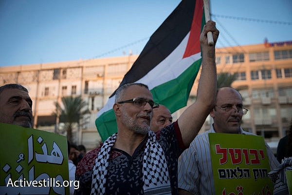 A Palestinian citizen of Israel waves a Palestinian flag during a protest against the Jewish Nation-State Law, central Tel Aviv, August 12, 2018. (Oren Ziv/Activestills.org)