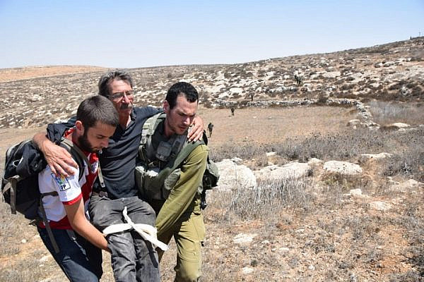 A Ta'ayush activist is carried away after being attacked by settlers in the illegal outpost of Mitzpe Yair, South Hebron Hills, August 25, 2018. (Nasser Nawaja/B'Tselem)