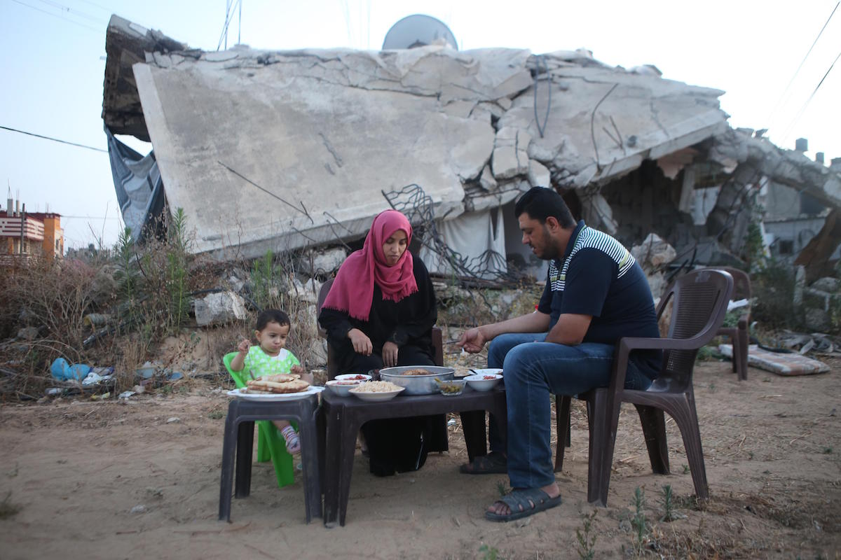 The Shaheen family shares a meal next to the rubble of their house, which was destroyed in Israel's 2014 military offensive on Gaza. They haven't been able to reconstruct it since. (Mohamed Al Hajjar)