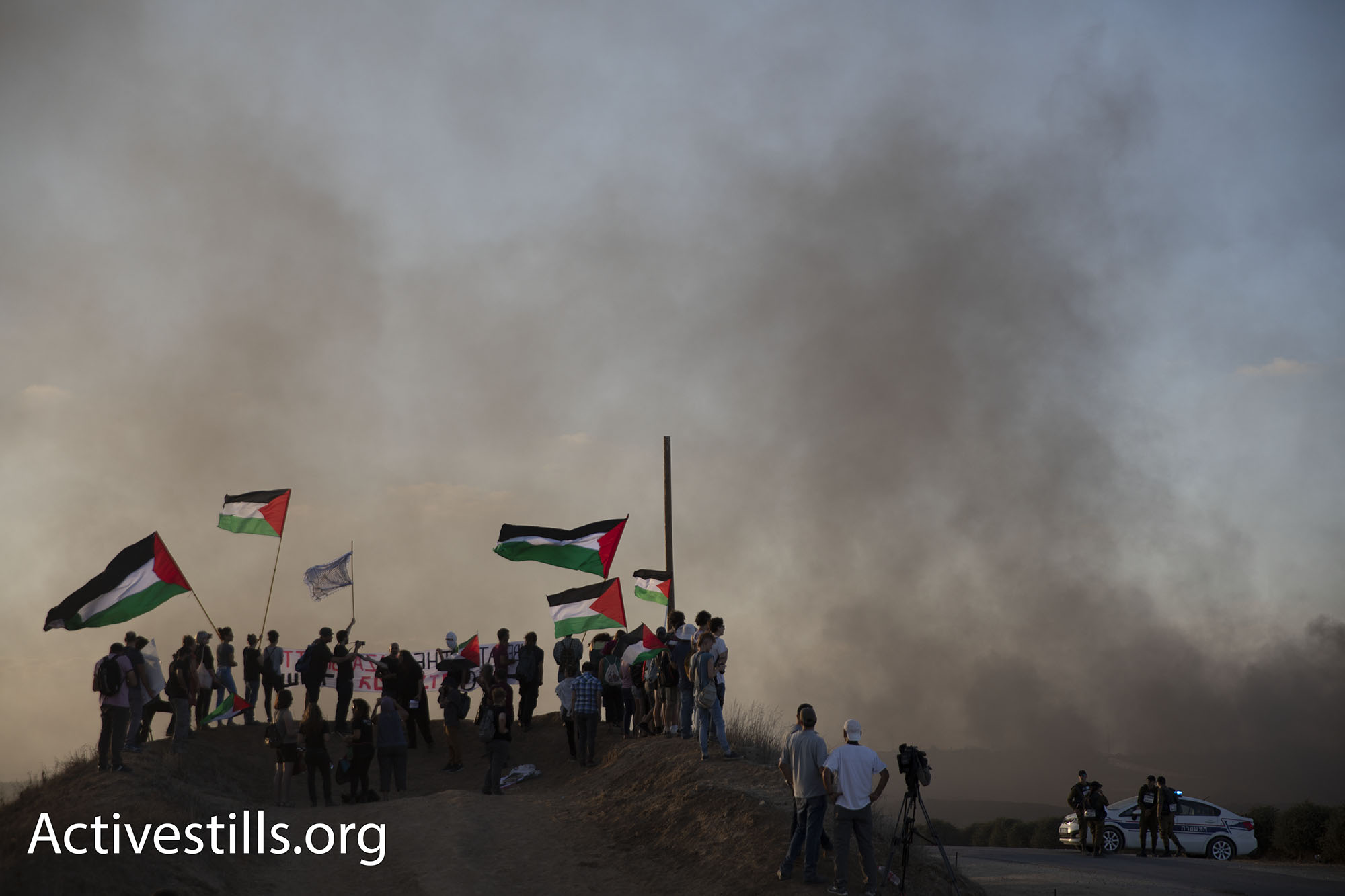 Activists on the Israeli side of the Gaza fence could see the smoke from burning tires, smell tear gas, and hear gunshots that Israeli soldiers fired at Palestinian protesters. (Oren Ziv/Activestills.org)
