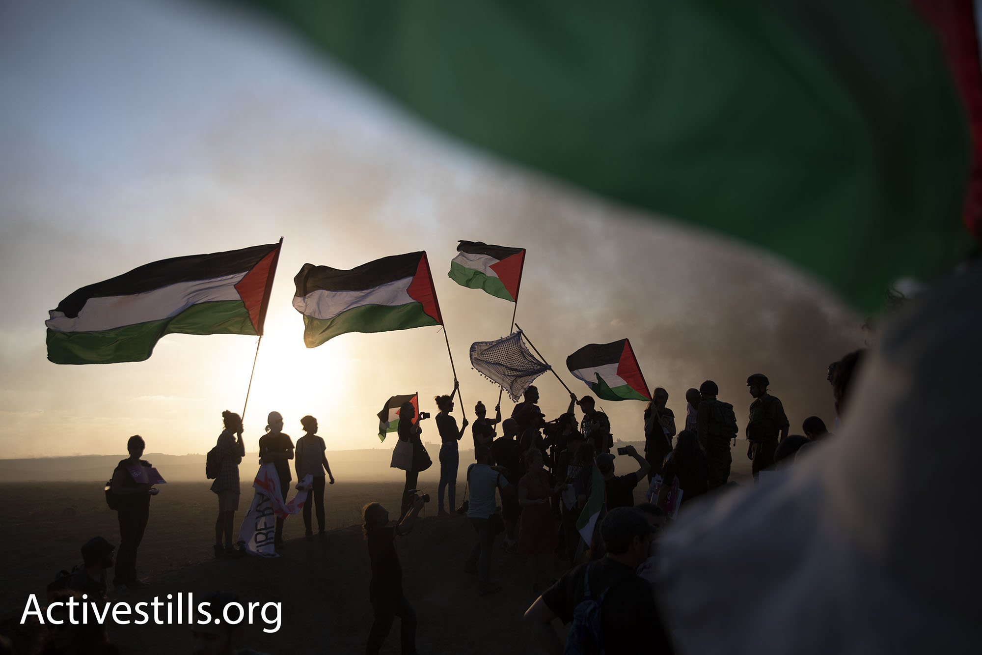 Dozens of Israeli and Palestinian activists protested on the Israeli side of the Gaza fence in solidarity with the Great Return March. Palestinian demonstrators responded with cheers of joy at the sight of the Palestinian flags. (Oren Ziv/Activestills.org)