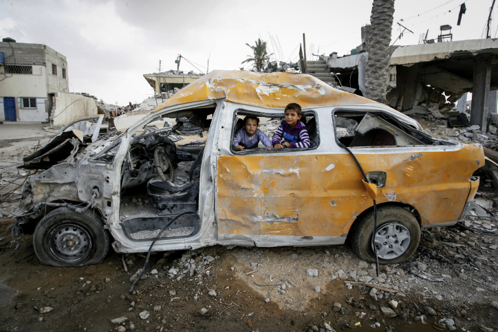 Palestinian children play in a car that, according to witnesses, was damaged during a seven-week Israeli offensive in Khuza'a, east of Khan Younis, in the southern Gaza Strip, on Oct. 19, 2014. (Abed Rahim Khatib/Flash90)