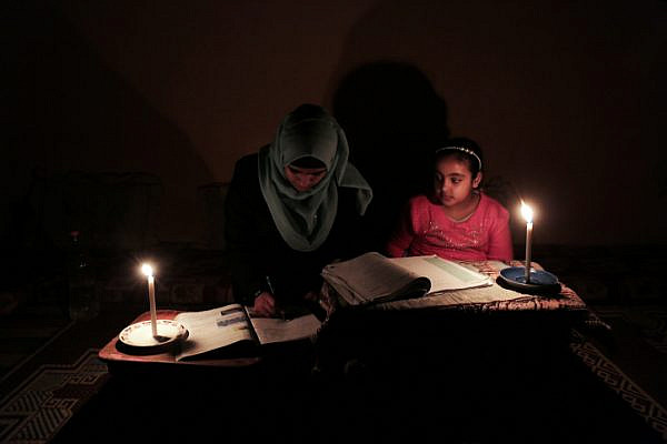 Palestinian children do their homework by candlelight at their home in Rafah refugee camp, in the southern Gaza Strip, on February 15, 2018. (Abed Rahim Khatib/ Flash90)