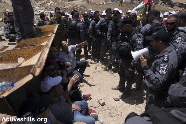 Palestinian, foreign, and Israeli activists try to block an Israeli bulldozer preparing for the demolition of Khan al-Ahmar, July 4, 2018. (Oren Ziv/Activestills.org)