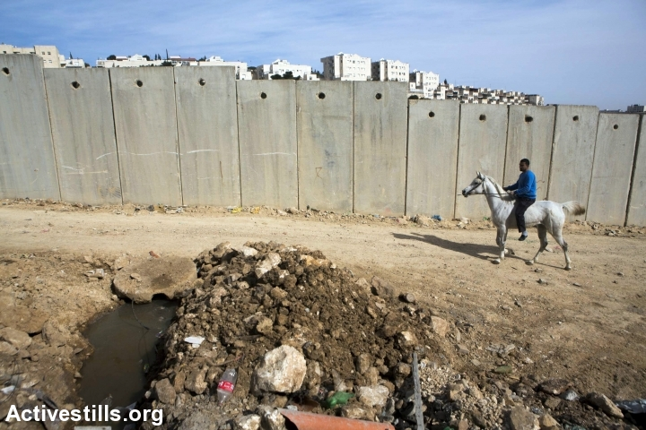 The separation wall in Shuafat refugee camp, in the background is Israeli settlement of Pisgat Ze'ev, East Jerusalem, January 24, 2017. (Anne Paq/Activestills.org)