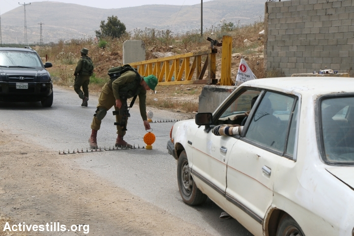 Israeli soldiers inspect Palestinian cars at the Beit Furik checkpoint, near Nablus, West Bank, May 27, 2015. (Ahmad Al-Bazz/Activestills.org)