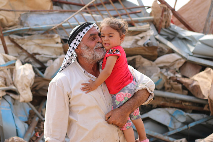 A Palestinian man plays with his daughter in front of his residential structure following an Israeli demolition in Al Hadidiya, Jordan Valley, West Bank, October 11, 2018. (Ahmad al-Bazz/Activestills.org)