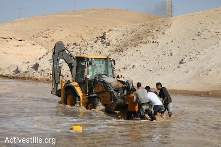 Palestinian and Israeli activists block a bulldozer in the West Bank village of Khan al-Ahmar, October 15, 2018. (Oren Ziv/Activestills.org)