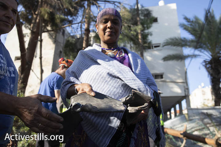 An Ethiopian-Israeli woman holds up shrapnel from a rocket fired from the Gaza Strip that exploded in the southern Israeli city of Ashkelon, November 13, 2018. (Oren Ziv/Activestills.org)