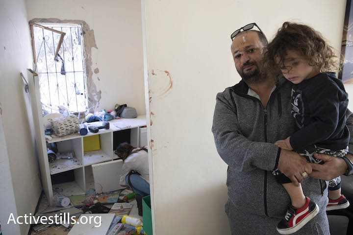 An Israeli man and his daughter seen after their house was hit by a rocket fired by Palestinians in the Gaza Strip, Ashkelon, southern Israel, November 13, 2018. (Oren Ziv/Activestills.org)