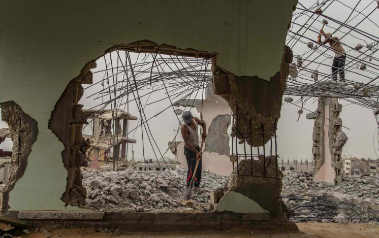 A Palestinian laborer works amongst the rubble of destroyed Palestinian houses, damaged during the 2014 war on Gaza, September 9, 2015. (Emad Nassar/Flash90)