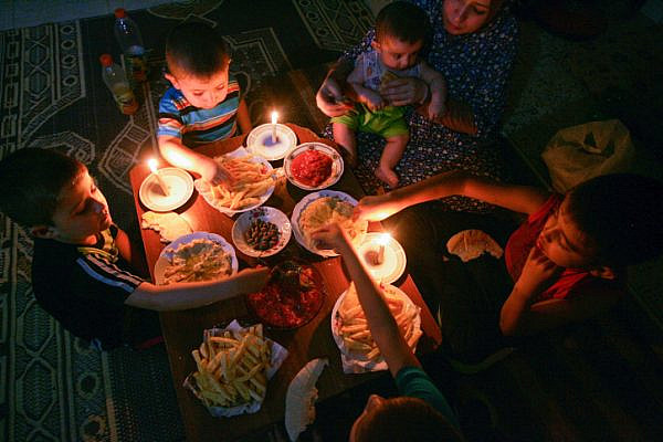 A Palestinian family eats dinner by candlelight at their home in Rafah, in the southern Gaza Strip, during a power outage on June 12, 2017. (Abed Rahim Khatib/Flash90)