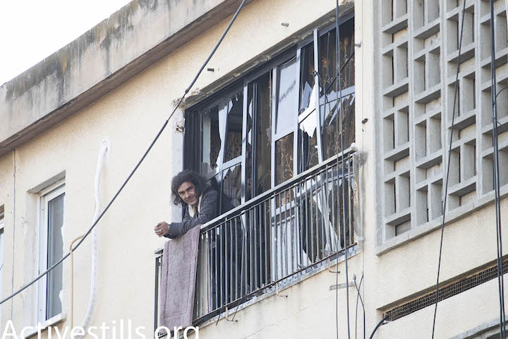 An Israeli in the city of Ashkelon looks on from his apartment following a night of rocket attacks on southern Israel, November 13, 2018. (Oren Ziv/Activestills.org)