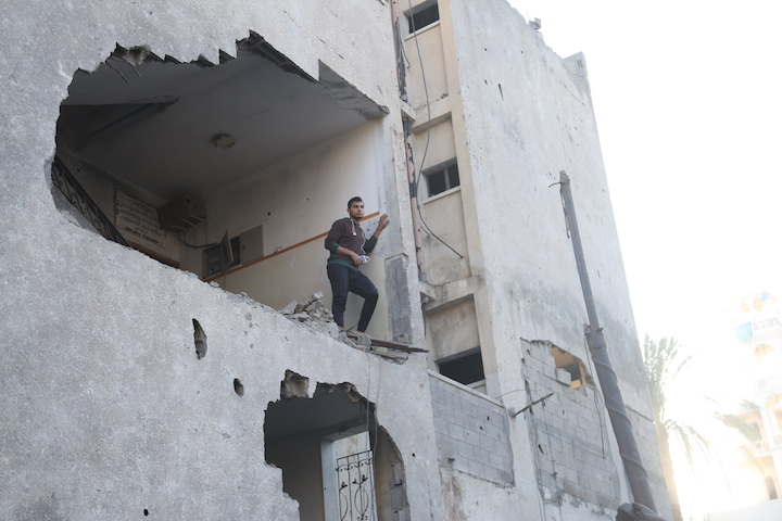 A Palestinian man looks on from the remains of a building that housed the Al Aqsa television station, following an Israeli air strike, November 13, 2018. (Mohammad Zaanoun)