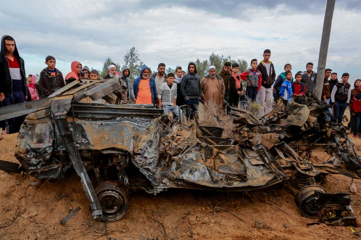 Palestinians stand next to the remains of a car destroyed during fighting between Hamas militants and Israeli special forces in Khan Younis, Gaza Strip, November 12, 2018. (Abed Rahim Khatib/Flash90)