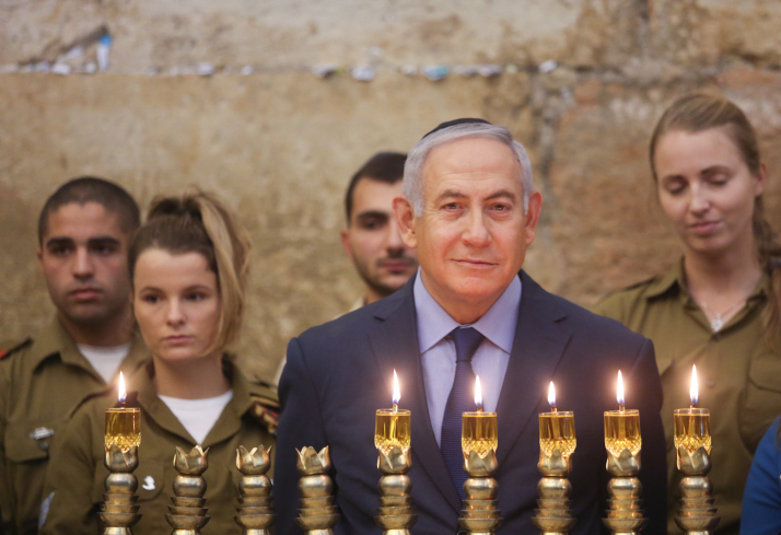 Israeli Prime Minister Benjamin Netanyahu lights the 'Hanukkia' on the First night of the Jewish holiday of Hanukkah at the Western Wall in Jerusalem, December 06, 2018. (Marc Israel Sellem/GPO)