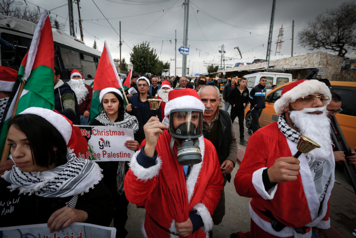 Palestinians dressed up in Santa Claus costumes take part in a protest at an Israeli checkpoint in the West Bank city of Bethlehem, a day before Christmas, December 23, 2018. (Wisam Hashlamoun/Flash90)