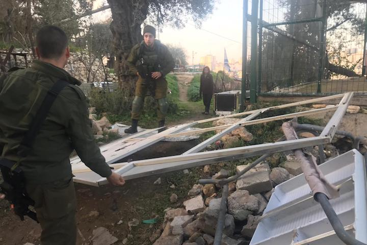 Israeli soldiers remove a makeshift fence used by Hebron human rights activist Issa Amro to protect his home from settler attacks, December 26, 2018. (Issa Amro)