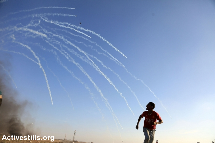 Palestinians run from tear gas during a 'Great Return March' at the Gaza-Israel fence, east of Gaza city, August 10, 2018. (Mohammed Zaanoun/Activestills.org)