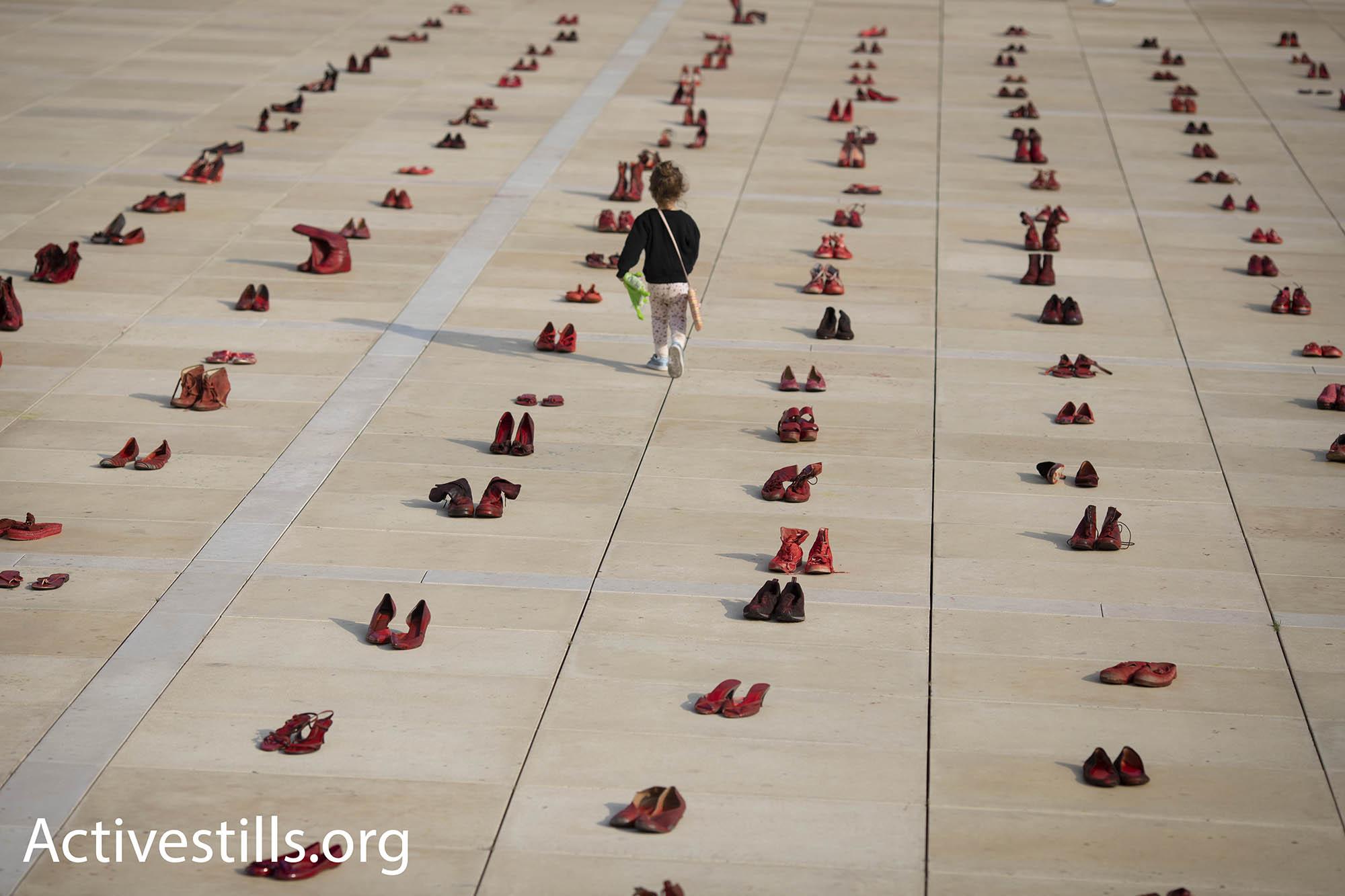 Feminist activists paint hundreds of pairs of shoes red to protest gender violence, Tel Aviv, December 4, 2018. (Oren Ziv/Activestills.org)
