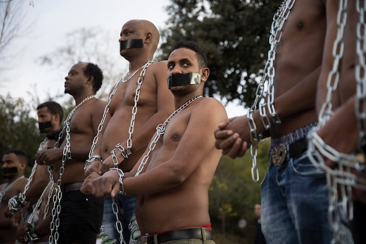 Eritrean asylum seekers and Israeli activists take part in a performance, acting slaves being traded in Libya, to protest against the planned deportation of asylum seekers by the Israeli government, outside of the Israeli parliament in West Jerusalem, January 17, 2018. (Oren Ziv/Activestills.org)
