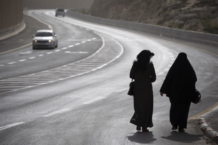 Palestinian women walk on the Palestinian side of Route 4370, known as the 'apartheid road,' just east of Jerusalem, West Bank. (Oren Ziv/Activestills.org)