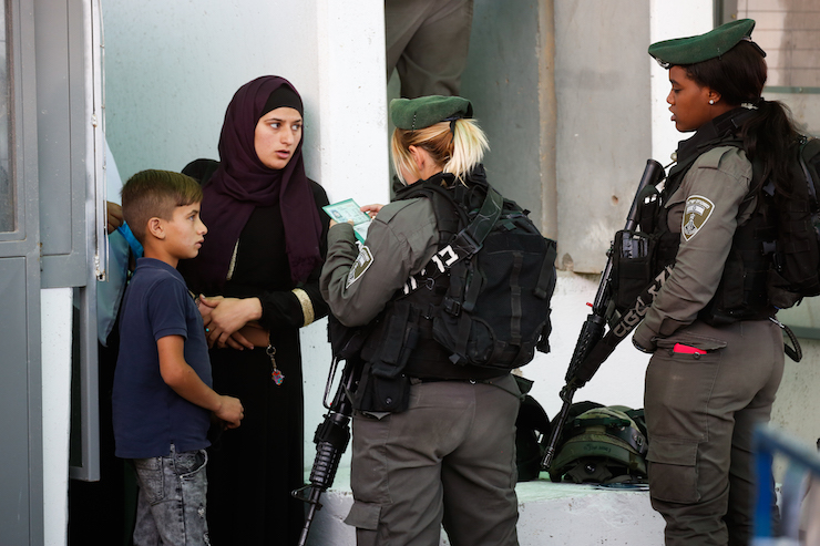Israeli troops check the ID of a Palestinian woman and her child at a checkpoint in the occupied West Bank, May 18, 2018. (Wisam Hashlamoun/Flash90)