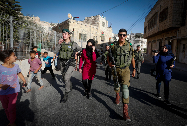 Israeli soldiers and Border Police officers arrest a Palestinian woman after she allegedly tried to cross a checkpoint with a knife, Hebron, West Bank, on September 27, 2017. (Wisam Hashlamoun/Flash90)