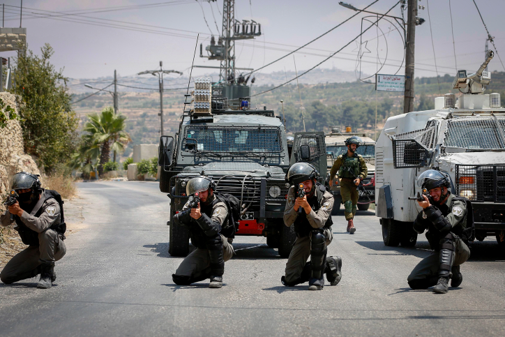 Israeli Border Police officers take positions during clashes with Palestinian protesters in the West Bank city of Hebron, July 14, 2018. (Wisam Hashlamoun/Flash90)