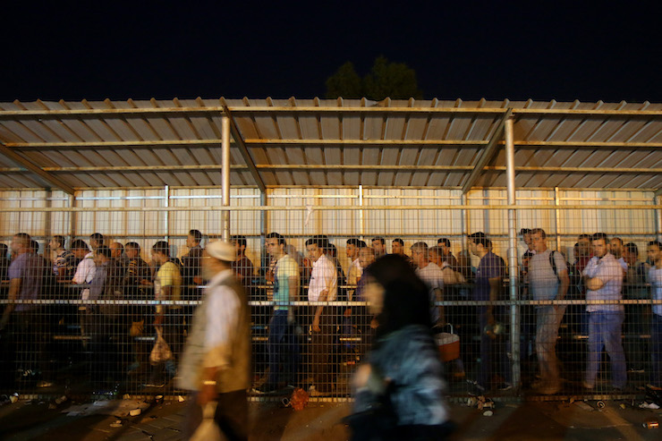 Thousands of Palestinian workers line up before dawn to pass through the Israeli army's 'Eyal Checkpoint' on their way to work in Israel, July 16, 2017. (Ahmad Al-Bazz/Activestills.org)