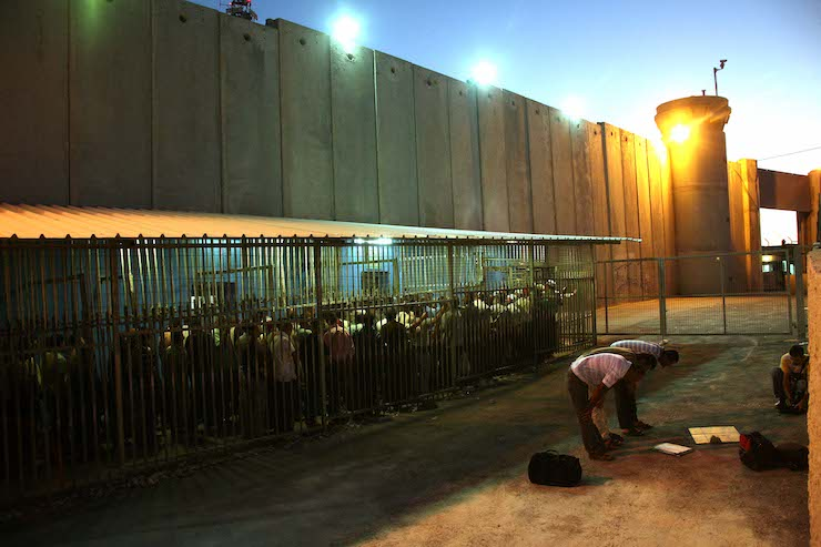 Palestinian workers wait to cross a checkpoint to work in Israel at the separation barrier in the West Bank city of Bethlehem, on August 23, 2010. (Najeh Hashlamoun/Flash 90)