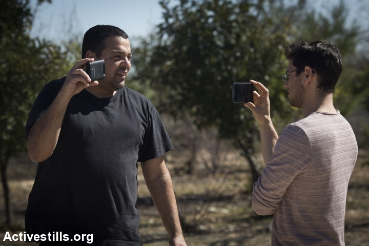 An Israeli settler (left) films a member of Breaking the Silence group during a tour in Hebron, West Bank, February 24, 2016. (Oren Ziv/Activestills.org)