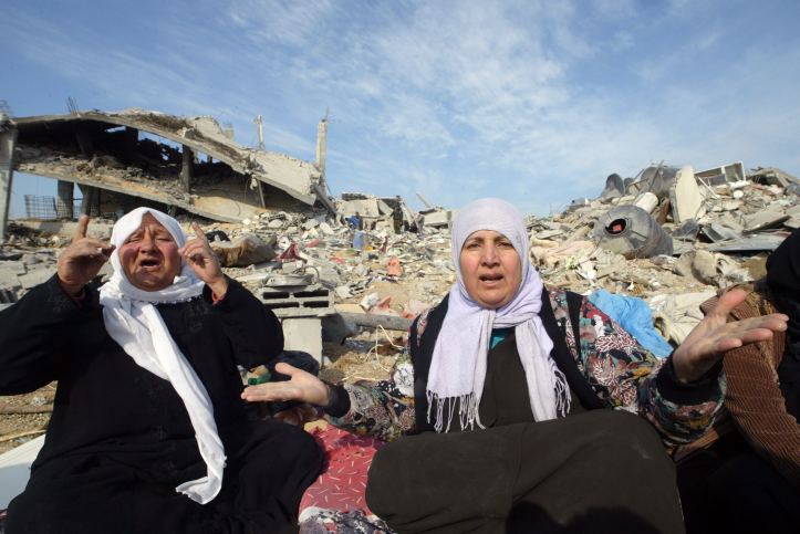 A Palestinian family sits in the rubble of their home during Operation Cast Lead, January 19, 2009, Jabaliya, Gaza Strip. (Abed Rahim Khatib/Flash90)